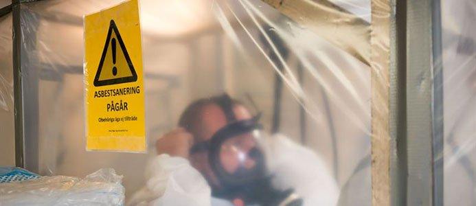 Man med ansiktsmask bakom plastskydd
