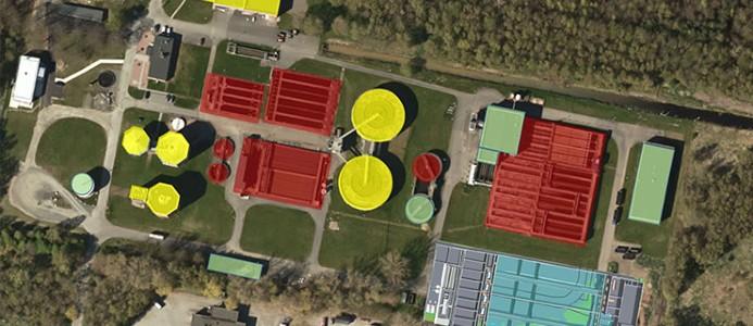 I bildens nedre högre hörn syns den nya samlade reningsanläggningen. De övriga byggnaderna som är grönmarkerade ska behållas, de gula byggas om för annan användning och de röda ska rivas. Bild: Kristianstads kommun